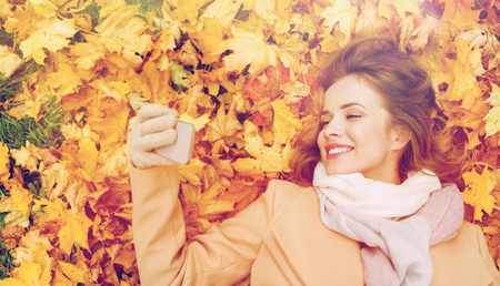 woman on autumn leaves taking selfie by smartphone photo