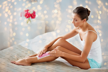 woman epilating leg hair with wax strip at home Stock Photo