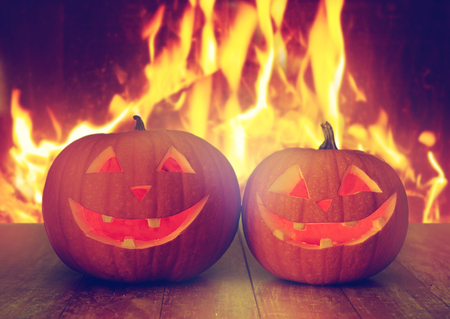 carved halloween pumpkins on table over fire Stock Photo