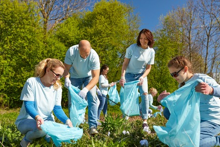 volunteers with garbage bags cleaning park area photo