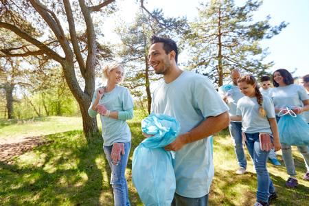 volunteers with garbage bags walking outdoors photo