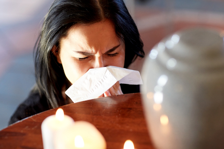 woman with cremation urn at funeral in church Stock Photo