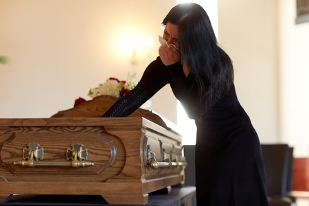 woman with coffin crying at funeral in church 版權商用圖片