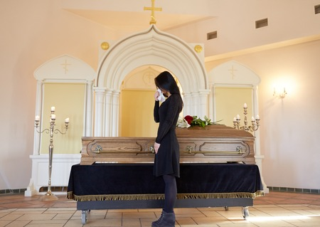 sad woman with coffin at funeral in church Banco de Imagens - 83942474