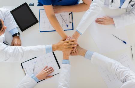 Groep artsen die handen bij elkaar houden aan tafel
