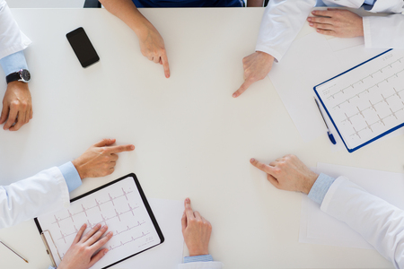 group of doctors with cardiograms working at table Stock Photo