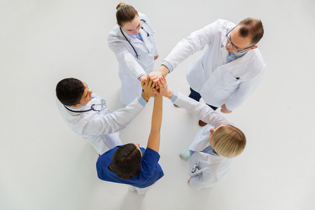 group of doctors making high five at hospital photo