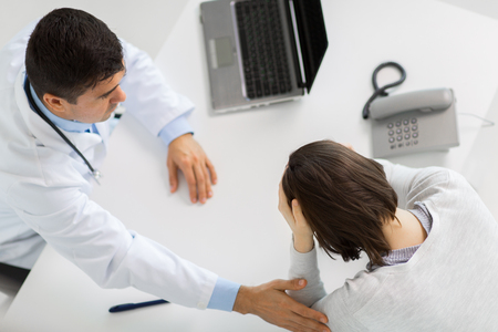 doctor with laptop and woman patient at hospital photo