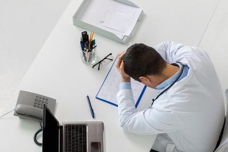 doctor with cardiogram and laptop at clinic photo
