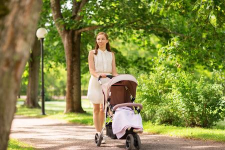 Gelukkige moeder met kind in kinderwagen op zomerpark