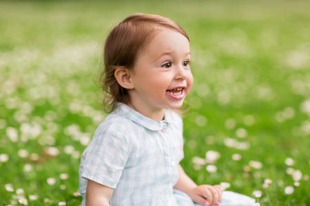 careless: happy baby girl on green summer field