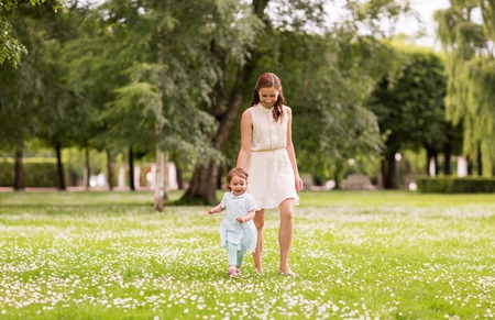 mother with baby girl walking at summer park