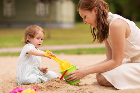 family, childhood and parenthood concept - happy mother and little baby girl with sand toys playing in sandbox at summer playground Stock Photo