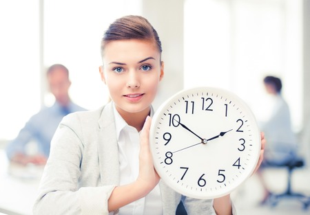 businesswoman showing white clock in office Stock Photo