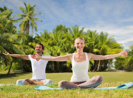 couple doing yoga in lotus pose outdoors photo