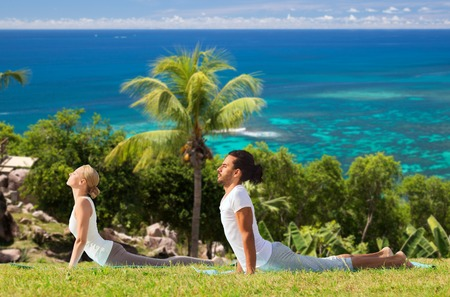 couple making yoga cobra pose outdoors photo