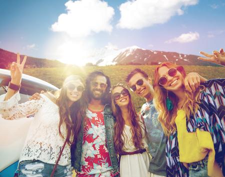 hippie friends over minivan car showing peace sign photo