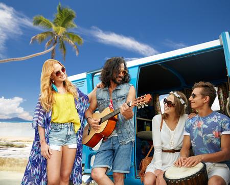 hippie friends playing music over minivan on beach photo