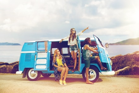 happy hippie friends in minivan car on island photo