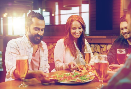 friends eating pizza with beer at restaurant photo