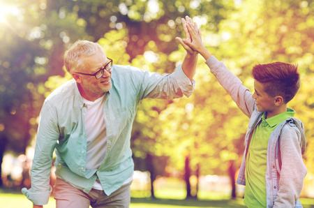 Alter Mann und Junge machen hoch fünf im Sommer Park Standard-Bild - 84086572