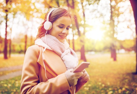 woman with smartphone and earphones in autumn park photo
