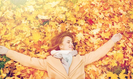 beautiful happy woman lying on autumn leaves photo