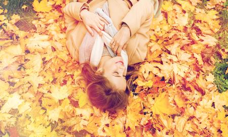 beautiful happy woman lying on autumn leaves photo