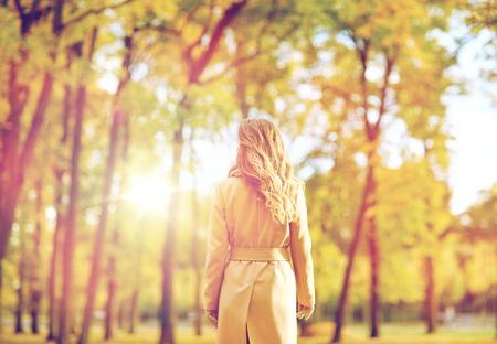 beautiful young woman walking in autumn park photo