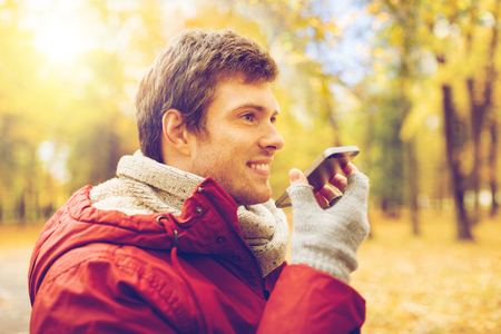 man recording voice on smartphone at autumn park photo