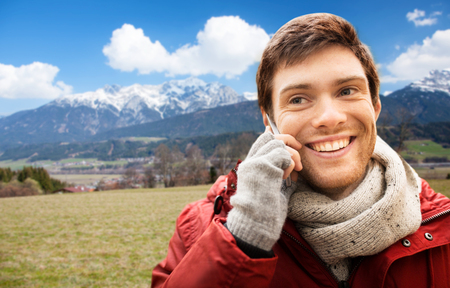 man calling on smartphone over alps mountains photo