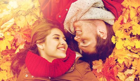close up of smiling couple lying on autumn leaves photo