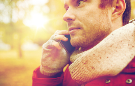 close up of man with smartphone calling in autumn photo