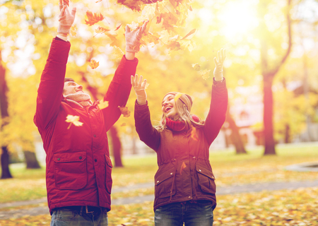 happy young couple throwing autumn leaves in park photo