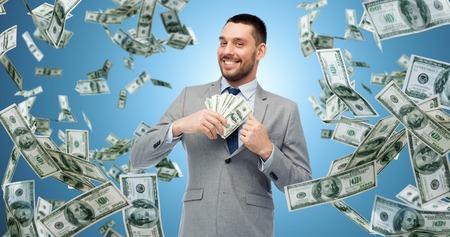アメリカのドルのお金を持ったビジネスマンを笑顔
