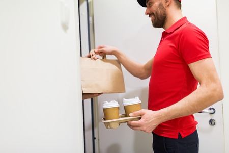 home, delivery service, mail and people concept - happy man delivering coffee and food in disposable paper bag to customer
