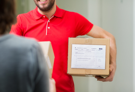 deliverer: home delivery service, mail, people and shipping concept - happy man delivering parcel box to customer Stock Photo