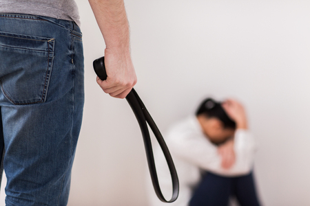 domestic violence, abuse and people concept - man beating helpless scared woman with belt