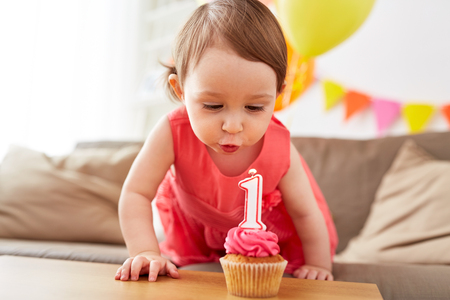 女の子の誕生日にケーキにろうそくを吹いて 写真素材