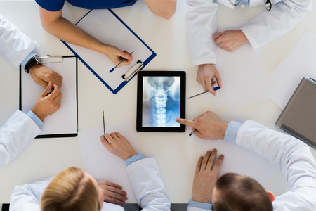 doctors with spine x-ray on tablet pc computer photo