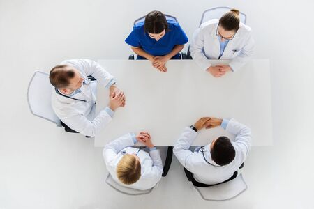 group of doctors sitting at empty table photo