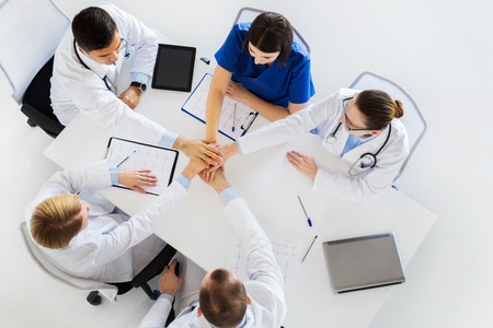 group of doctors holding hands together at table photo