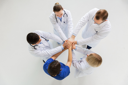 group of doctors with hands together at hospital photo