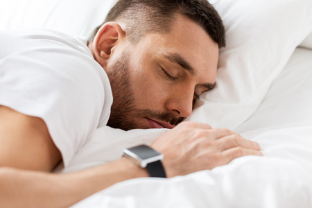 close up of man with smartwatch sleeping in bed photo