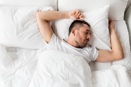 man sleeping in bed at home photo