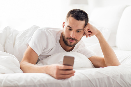 young man with smartphone in bed in morning photo