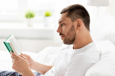 man reading book in bed at home photo