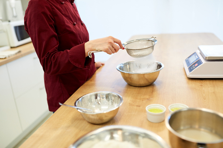 chef sifting flour in bowl making batter or dough