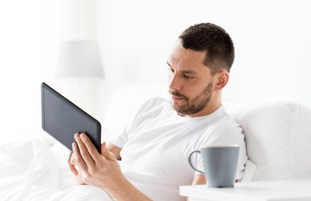 young man with tablet pc in bed at home bedroom photo