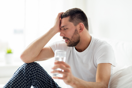 man in bed with glass of water at home photo